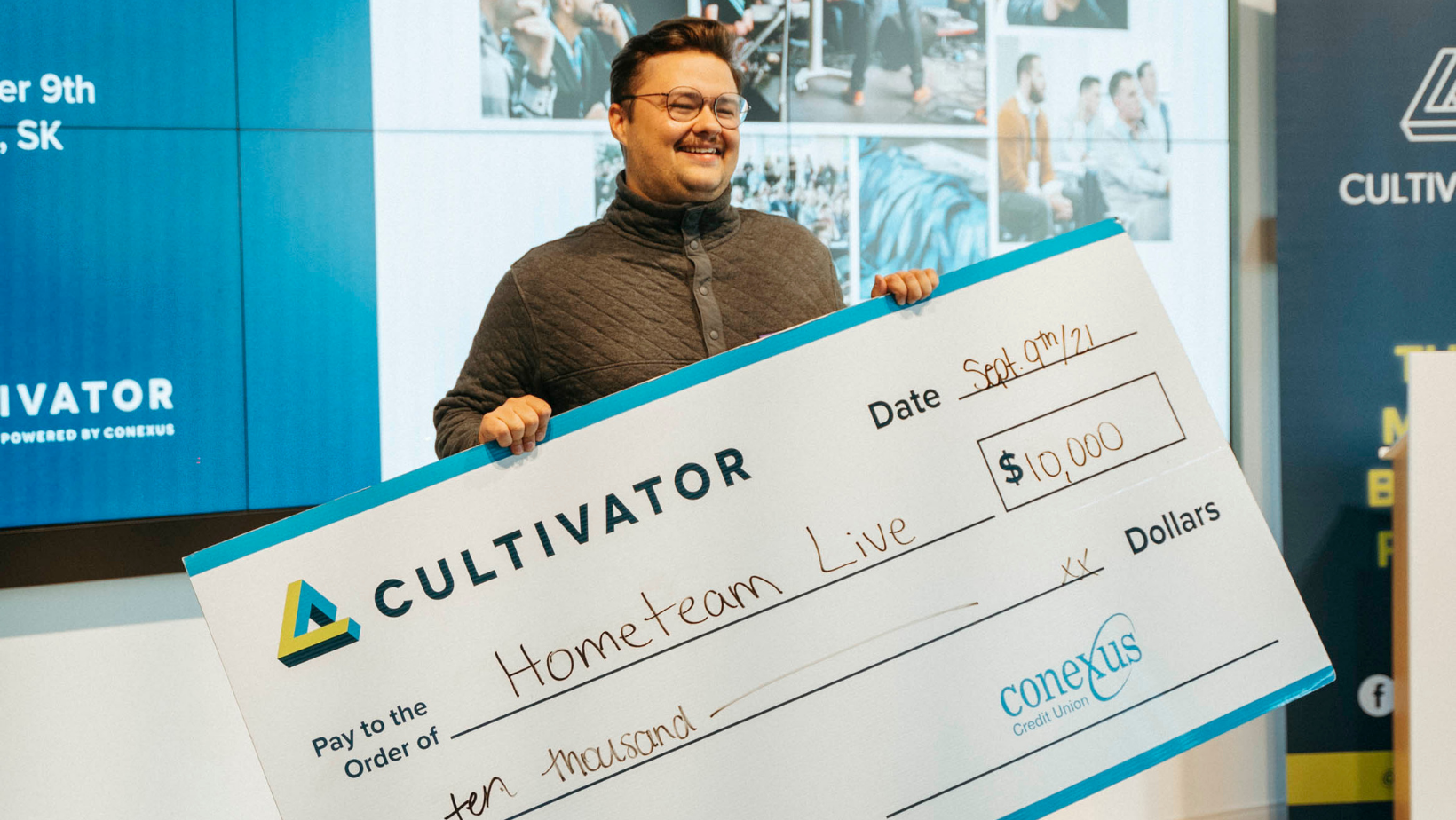 Tanner Goetz, founder of HomeTeam Live, smiling with $10,000 cheque